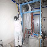 Worker taking asbestos material off a wall